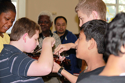 Photo of PA students helping sight impaired child play violin