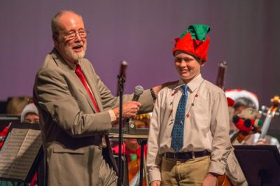 Photo of Dr. Partridge on stage with student wearing an elf hat and Christmas lights