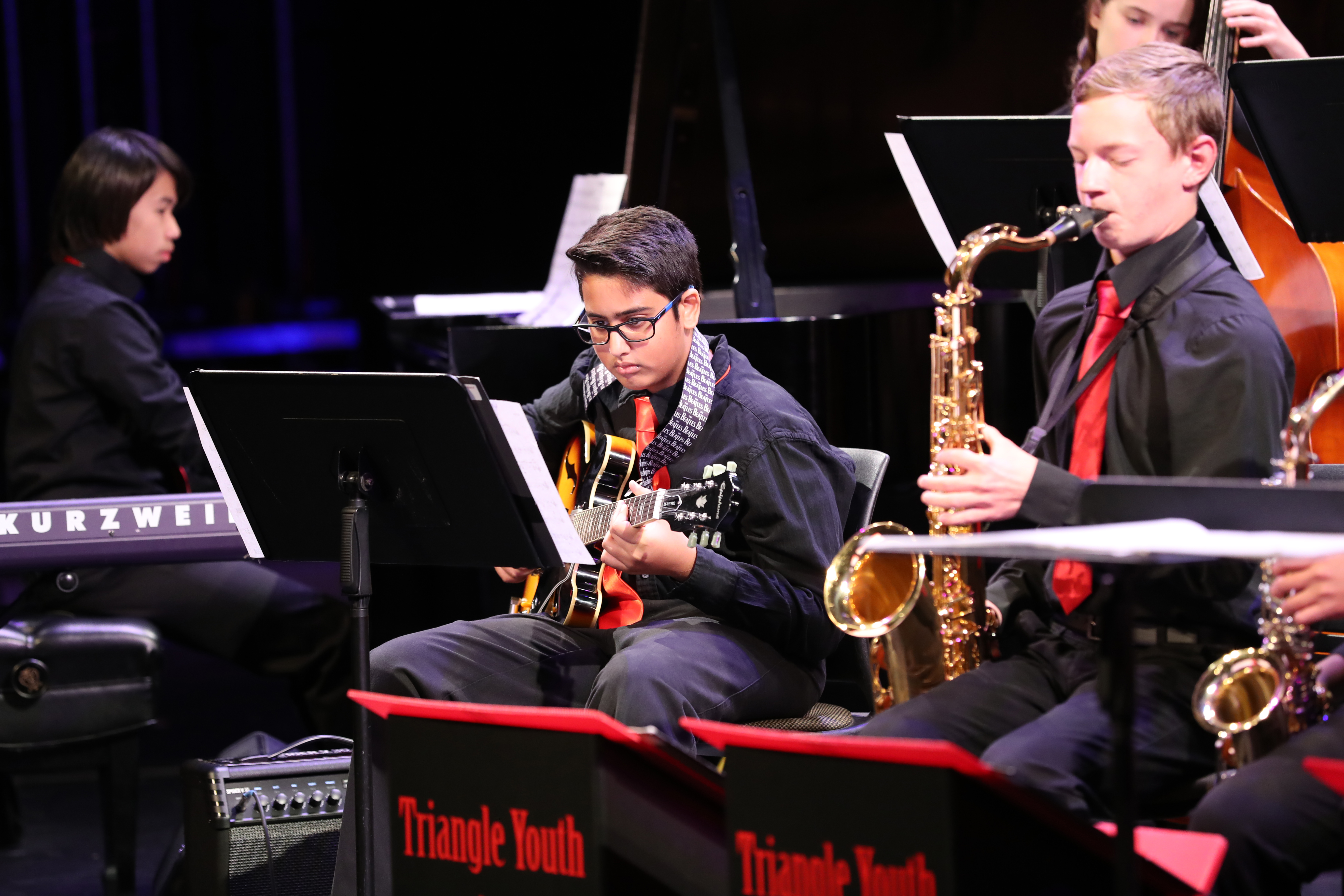 photo of jazz band saxophonist, guitarist, and pianist in action
