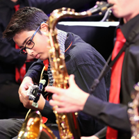 Close up photo of a saxophonist and a guitarist during a jazz concert