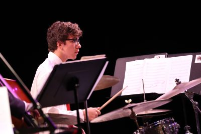 Photo of jazz ensemble drummer in action