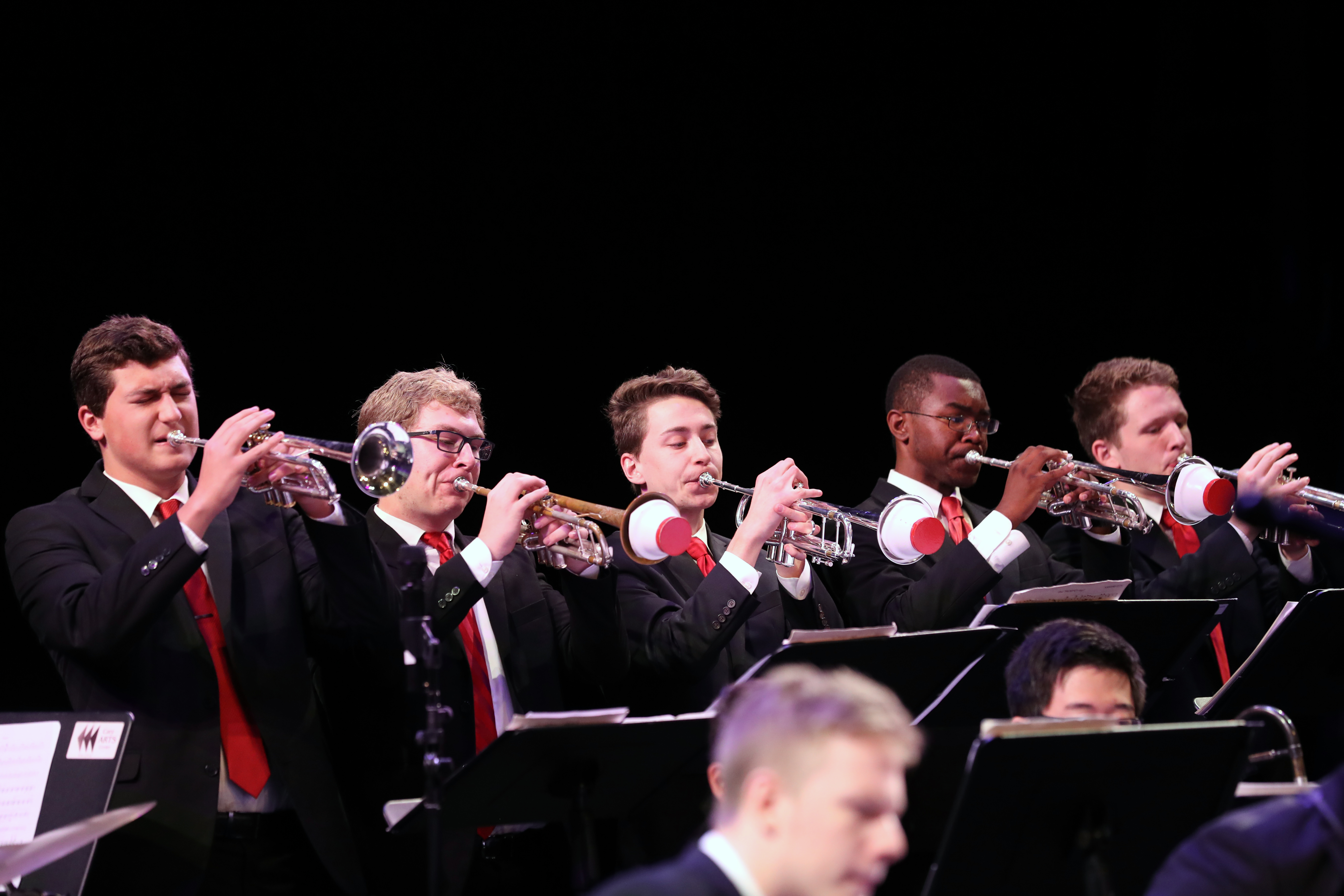 photo of jazz ensemble trumpet section with cup mutes in during concert
