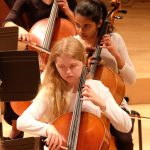 Photo of three symphony cellists during a performance