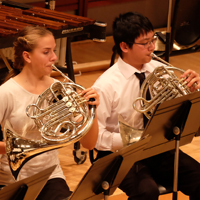 Photo of two french horn players during symphony concert