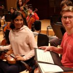 Photo of two smiling musicians during philharmonic dress rehearsal