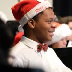 """Photo of smiling musician wearing a santa hat that says """"merry christmas"""""""