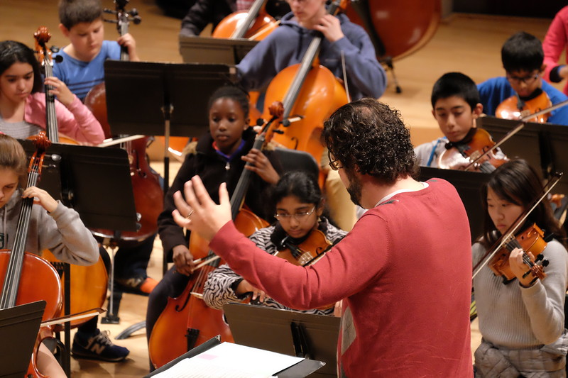 Photo of conductor and musicians and musicians at dress rehearsal