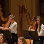 Photo of two harpists during a symphony concert