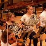 Photo of french horn section at symphony concert