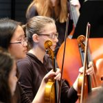 photo of violinists and a double bassist at sinfonia concert