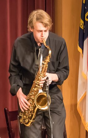 Photo of saxophonist playing a solo during a jazz concert.