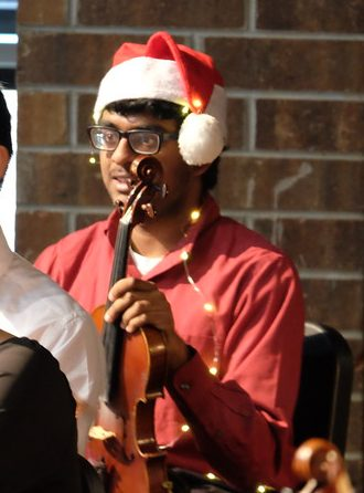 Photo of a violinist wearing a Santa Claus hat and Christmas lights at a Christmas concert