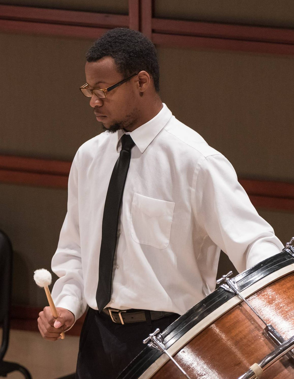 Photo of a percussionist playing the bass drum at a performance