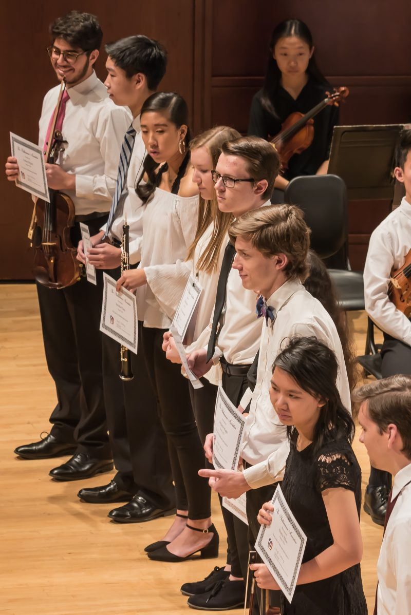 Photo of orchestra musicians graduating during a performance in 2018.