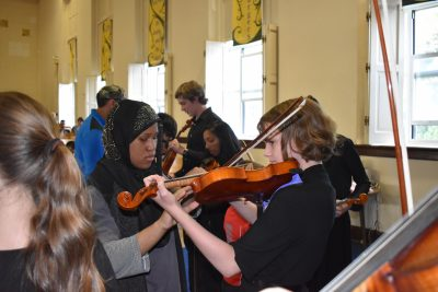 Photo of PA student letting sight impaired woman feel her violin as she plays.