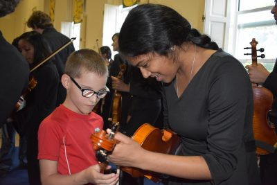 Photo of PA student letting sight impaired child feel her violin as she teaches him about it.