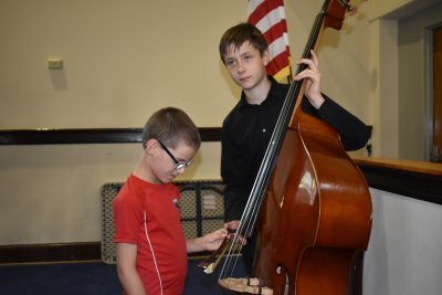 Photo of PA student letting a sight impaired child hold his double base bow as he plays.