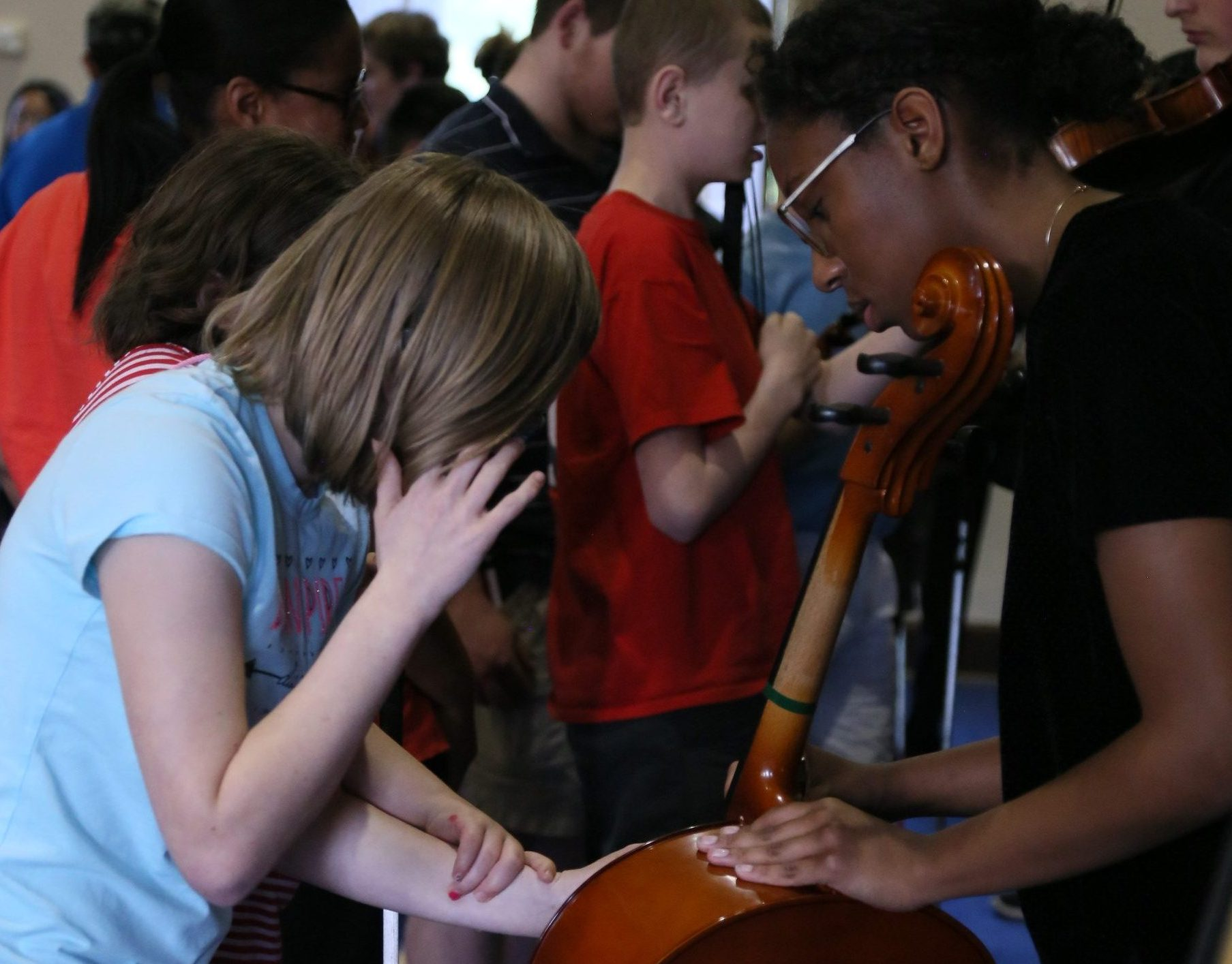 Photo of PA student letting sight impaired child feel her cello.