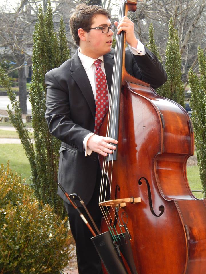 alumni Philip Norris stands with his bass
