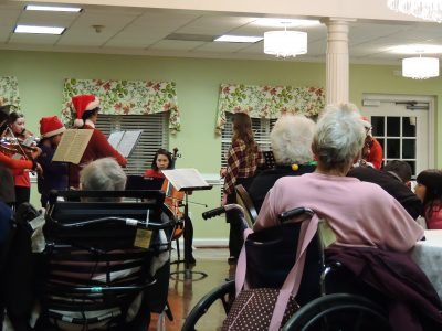 Residents at Hillcrest Retirement Comunity watch Philharmonic Association Holiday Ensemble's Performance