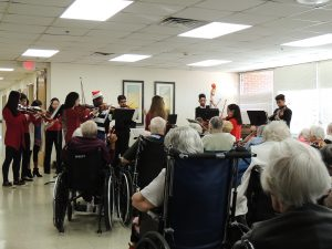 musicians perform holiday music for a nursing home