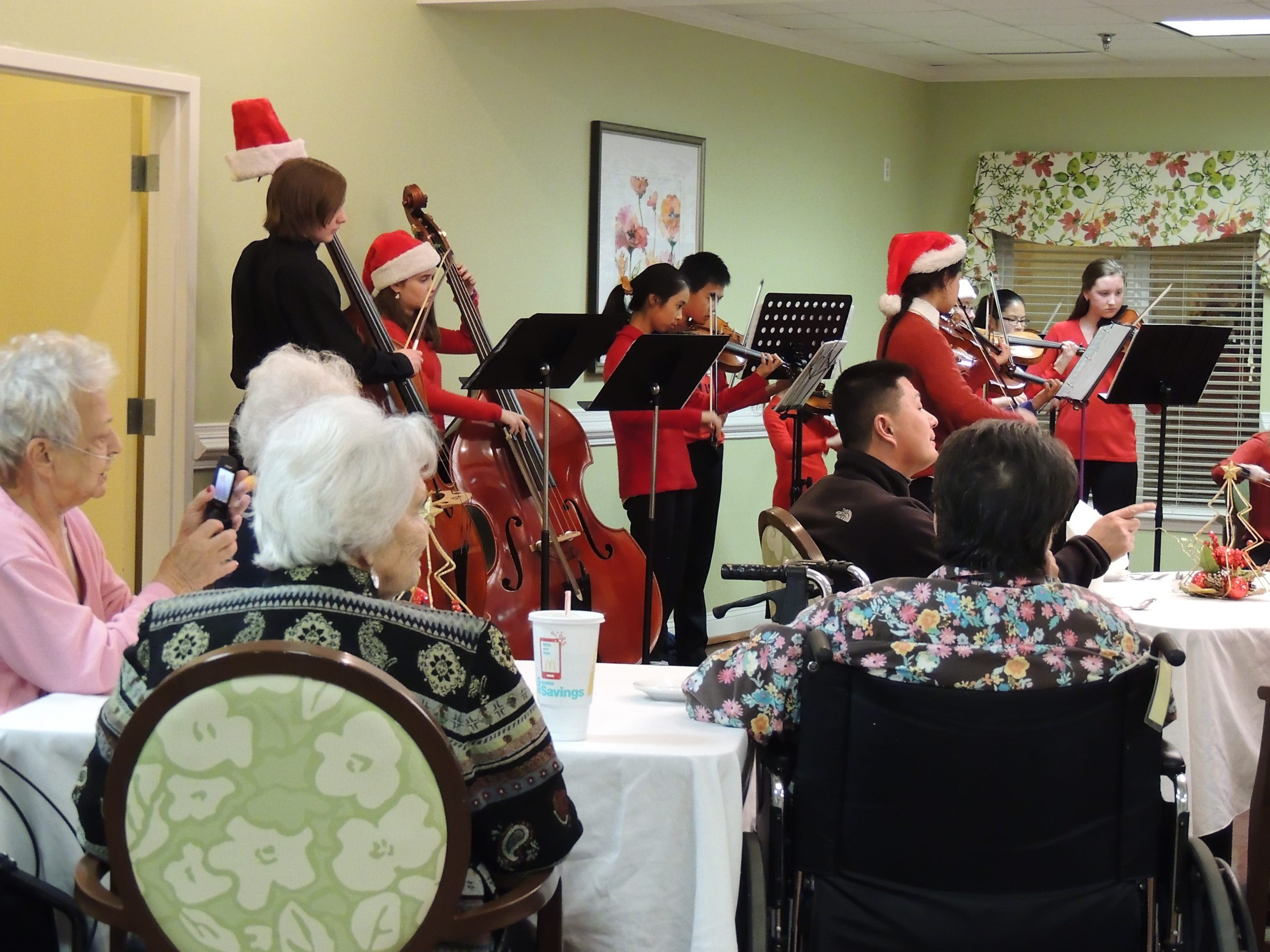 Young musicians playing for seniors in nursing home