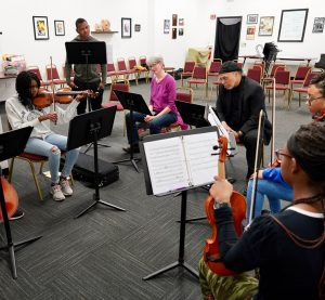 Photo of Margaret working with Elmber Gibson and the United Strings of Color